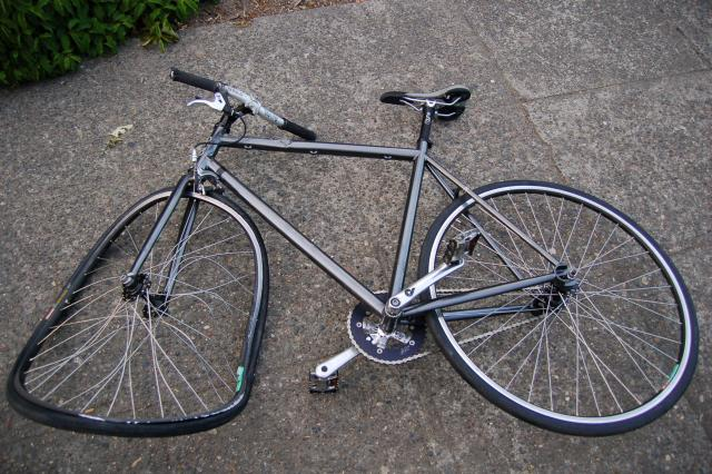 Fixed gear bike with tacoed wheel and badly bent handlebars